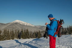 Hiker man standing on the background of winter mountains Royalty Free Stock Images