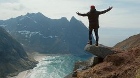 Hiker man with a standing on the edge of the mountain in Norway in with strong wind. Norway lofotet stock footage