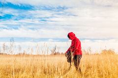 Hiker man standing in the field and putting his water bottle in a backpack Stock Photos