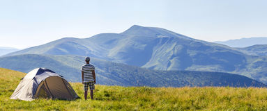 Hiker man standing near camping tent in carpathian mountains. To Stock Image
