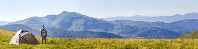 Hiker man standing near camping tent in carpathian mountains. To. Urist enjoy mountain view. Travel concept Royalty Free Stock Images