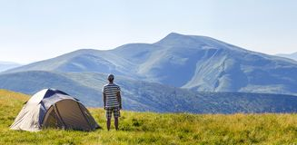 Hiker man standing near camping tent in carpathian mountains. To. Urist enjoy mountain view. Travel concept Stock Image