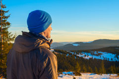 Hiker man standing in winter mountains looking into the distance Stock Image
