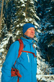 Hiker man standing in the winter wood on the background of snow- Stock Image