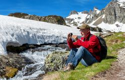 Hiker man take a picture with action camera stock photography