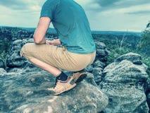 Hiker man take rest on peak. Male legs on sharp summit royalty free stock photos