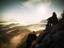 Hiker man take a rest on mountain peak. Man lay on summit, bellow autumn valley. Stock Image