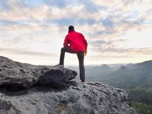 Hiker man take a rest on mountain peak. Man lay on summit, bellow autumn valley Royalty Free Stock Photos