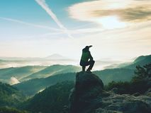 Hiker man take a rest on mountain peak. Man sit on sharp summit and enjoy spectacular view. Colorful autumn landscape. Bright morning Sun shining in sky Royalty Free Stock Photos