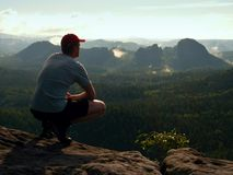 Hiker man take a rest on mountain peak. Man sit on summit, Stock Images