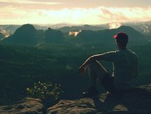 Hiker man take a rest on mountain peak. Man sit on summit, Royalty Free Stock Photo