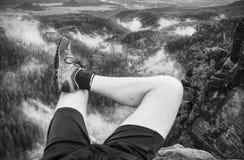 Hiker man take rest on peak. Male legs on sharp summit royalty free stock photography