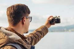 Hiker man takes photographs self portrait on coastline Stock Photos