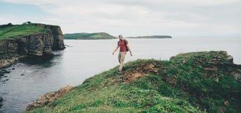 Hiker man walking on coastline near the sea Stock Photography
