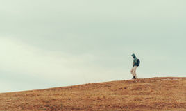 Hiker man walking down on the hill Stock Photos
