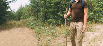 Hiker man walking with a wooden stick on footpath Royalty Free Stock Photography