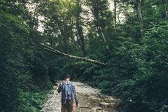 Hiker Man Walks Along Mouth Of Mountain River In Deep Forest, Rear View. Trek Hiking Destination Experience Lifestyle Concept Stock Photo