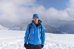 Hiker Man Wearing Sunglasses With Backpack Standing On A Background Of Snow-capped Mountains Royalty Free Stock Photos