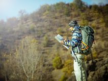 Hiker with map exploring wilderness on trekking adventure Royalty Free Stock Images