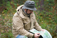 Hiker with map in forest Royalty Free Stock Images