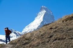Hiker and Matterhorn. A hiker on a trail looking at the Matterhorn in the distance Royalty Free Stock Photo