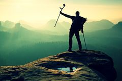 Hiker with  medicine crutch above head achieved mountain peak. Stock Photos