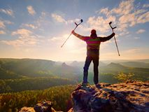 Hiker with  medicine crutch above head achieved  personal target. Broken knee. Hiker with  medicine crutch above head achieved  personal target. Broken leg fixed Stock Photo