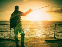 Lens defect. Hiker with medicine crutch and leg fixed in immobilizer walk stock images