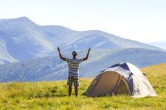 Hiker meets good morning with raised hands just got out from tent in mountains. Panoramic view of hiker who meets good morning with raised hands just got out royalty free stock photos