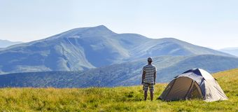 Hiker meets good morning with raised hands just got out from tent in mountains. Panoramic view of hiker who meets good morning with raised hands just got out royalty free stock images