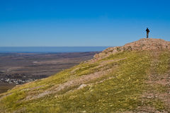 Hiker in the mountain. Hiker standing on mountain summit in sunny weather Royalty Free Stock Photography