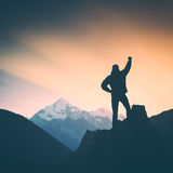 Hiker and the mountain. Instagram stylisation. Hiker who conquered the top of mountain standing on a cliffs edge with raised hand and enjoying sunrise above Stock Image