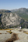 Hiker at Mountain Overlook. A hiker pauses to view the spectacular scenery on the cliffs overlooking Lysefjord, Norway Stock Photos