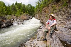 Hiker & mountain river. The young hiker has a rest at the mountain river Royalty Free Stock Images