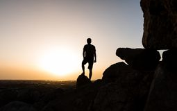 Hiker on the mountain top facing the sunset. Silhouette shoot royalty free stock image