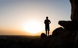 Hiker on the mountain top facing the sunset. Silhouette shoot stock image