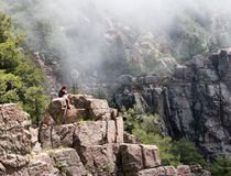 Hiker in mountains. Hiker sitting on a cliff using her cell phone Royalty Free Stock Photo