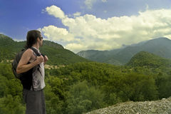 Hiker in mountains. Young man in shorts and with bachpack looks at faraway mountains covered with clouds Stock Photography