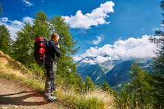 Hiker in the mountains. Hiker in the Apls mountains. Trek near Matterhorn mount. hiker stands on the trail, looks at the valley, and drinks water from the H2O Royalty Free Stock Photos