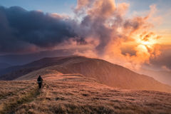 Hiker in mountains at breathtaking sunset Royalty Free Stock Photo