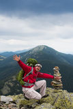 Hiker in mountains. Happy hiker winning reaching life goal, success, freedom and happiness, achievement in mountains. Stack of stones zen. Hiker with backpack on stock photos