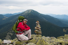 Hiker in mountains. Happy hiker winning reaching life goal, success, freedom and happiness, achievement in mountains. Stack of stones zen. Hiker with backpack on royalty free stock photography