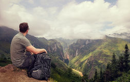 Hiker in mountains relaxing on top of a rock and enjoying view m Stock Photos