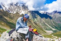 Hiker in the mountains watching the map on at rest Stock Images