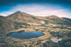 Hiker near the lake. Instagram stylisation. Tourist with backpack and trekking poles standing on a cliff near the mountain lake in a carpathian mountains Stock Photo