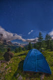 Hiker near a tent looking at the valley by night, Falzarego pass, Dolomites, Italy Stock Image