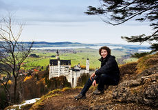Hiker and Neuschwanstein Castle. Hiker with Neuschwanstein Castle in the background, Bavaria, Germany stock photo