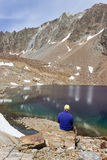 Hiker observes the spectacular color of Lac Mort, Valpelline, Aosta valley, Italy Stock Image