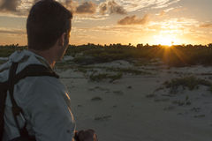 Hiker observes sunset Stock Photo
