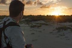 Hiker observes sunset stock photo